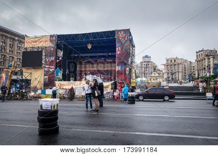 Two woman on a street in Kiev. Kiev, Ukraine - May 15, 2014: Two woman on a street at Freedom square Kiev stopped to look in a camera, in the background, empty stage with signs and a few people around.