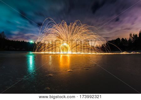 Trajectories of burning sparks on the surface of frozen lake at the background of spring night landscape