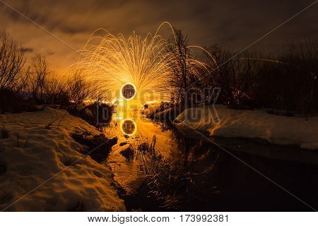 Abstract picture with trajectories of burning sparks on the surface creek at the background of spring night landscape