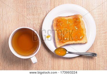 Toasted bread with apricot jam and a cup of black tea on table top view