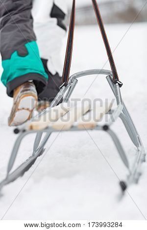 Low section of man with sled walking in snow