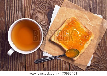 Toasted bread with apricot jam and a cup of black tea on wooden table top view
