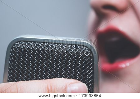 microphone/voice recorder closeup on a background of a singing girl with red lipstick