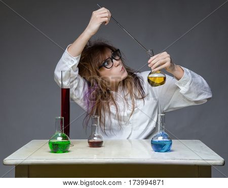 Working shaggy scientist in lab on gray background