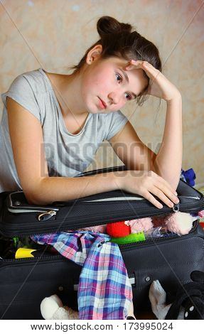 happy beautiful preteen girl packing coffer before the trip to the seaside land
