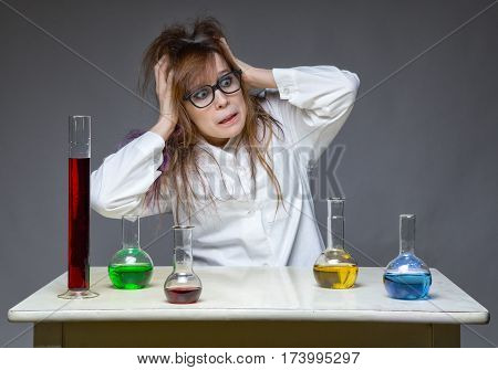 Guilty shaggy scientist woman in lab on gray background