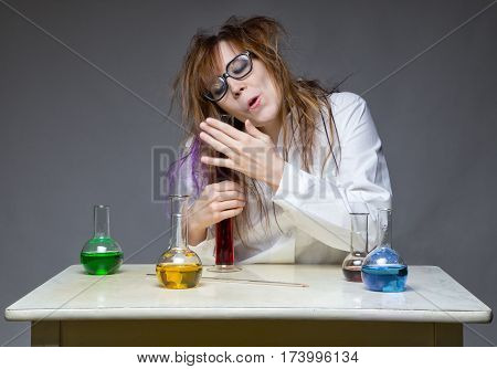 Kind shaggy scientist in lab on gray background