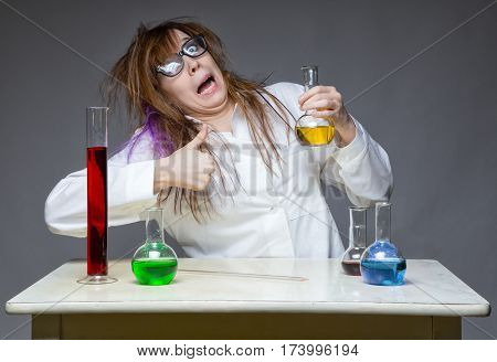 Shaggy scientist with thumb in lab on gray background