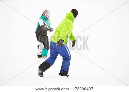 Full length of friends having snowball fight