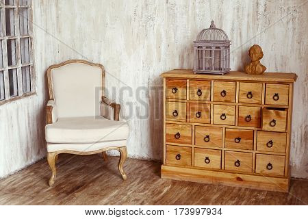 wooden chest of drawers in shabby styled room with bird cage and Mozart bust poster