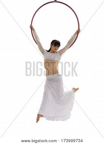 Young pretty brunette in white sexy top and long skirt perfoming exercises on aerial hoop in studio
