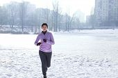 Sportive young woman running in winter park poster