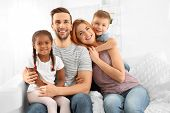 Happy interracial family sitting on sofa poster