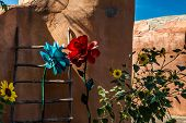 A kiva ladder and a mixture of real and artificial flowers decorate an adobe wall in Old Town Albuquerque New Mexico. poster