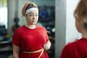 Portrait of cute obese woman standing against mirror in gym and measuring waist size with tape after workout, looking upset and confused poster