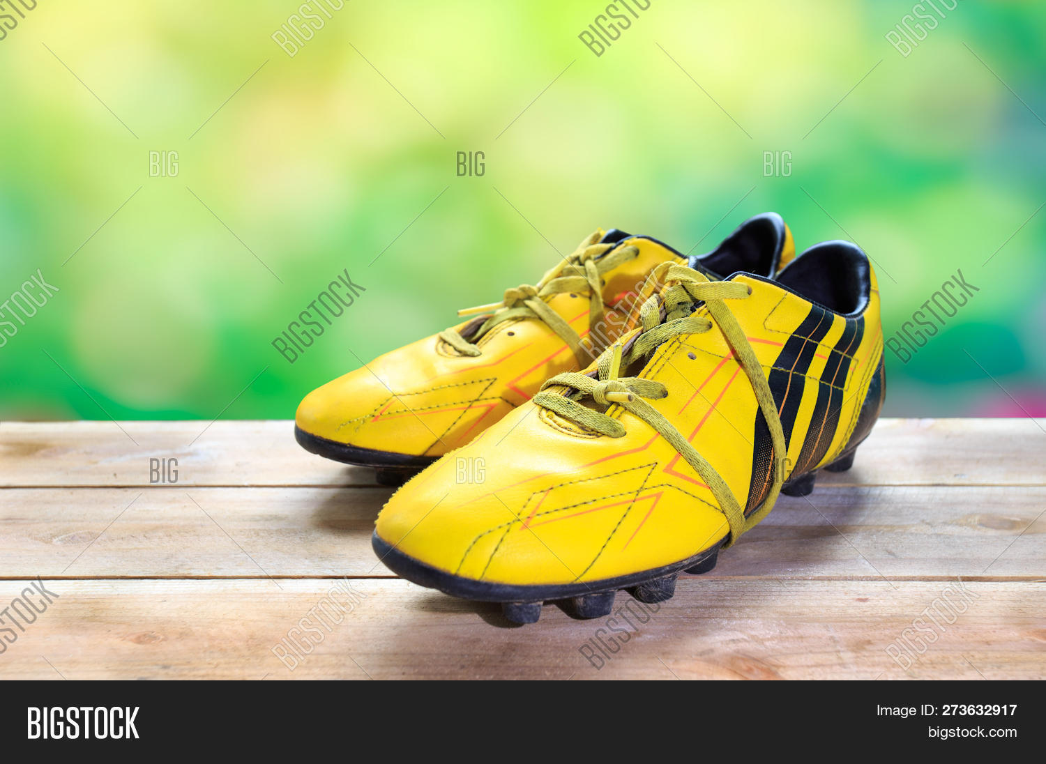 6455d0015 A Pair Of Football Boots Old Yellow Football Shoes Placed Natural Green  Background.
