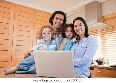 Happy young family with laptop standing in the kitchen together