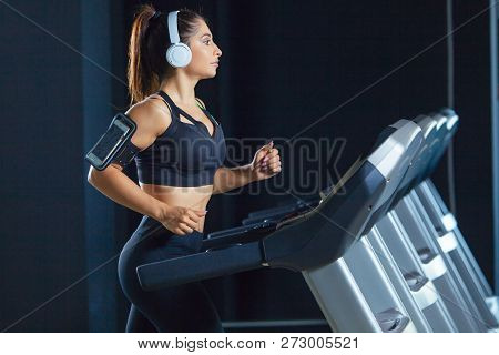 Young Fit Woman Running On Treadmill Listening To Music Via Headphone At Gym. Concept Of Healthy Lif