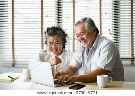 Relaxing Asian Senior Couple Having Fun With Laptop Computer Together At Their Apartment. Online Sho