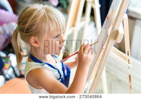 Cute Blond Smiling Girl Painting On Easel In Workshop Lesson At Art Studio. Kid Holding Brush In Han