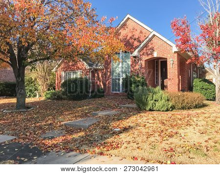 Sidewalk In Front Of American House In Fall Season With Colorful Autumn Leaves
