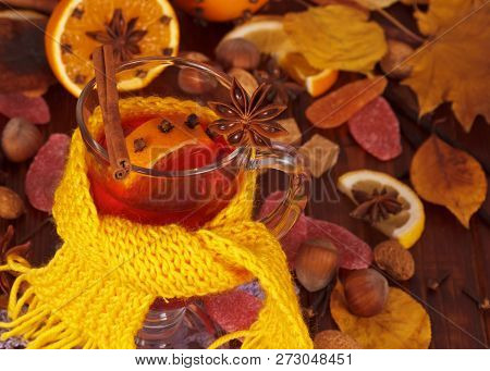 Top View. Glass Of Hot Mulled Wine Decorated With Bright Yellow Scarf In The Background Of The Spice