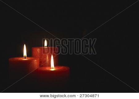 Closeup of burning candles isolated on black background
