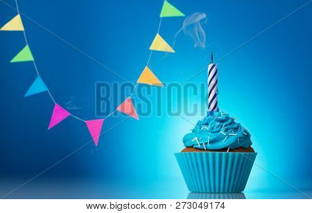 Chocolate Cupcake With Icing And Birthday Candle On Blue Background