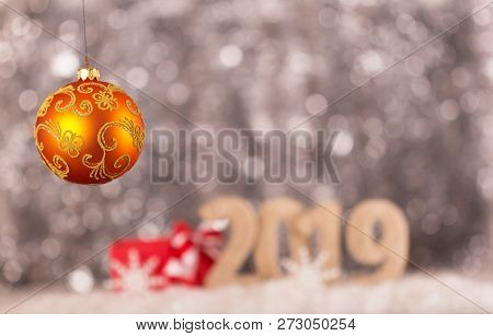 New Year Inscription 2019 With A Snow Background And Bright Yellow Christmas Ball