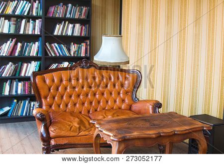 Classic Interior Room. Old Antique Leather Arm Chairs, Table And Bookshelves. Classic Decoration Wit