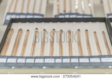 Gold Chains On The Showcase. Gold Jewelry. Gold Necklace In Red Background On Showcase Jewelry - Lux