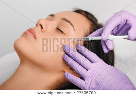 Woman receiving Botulinum Toxin Injection injection into eyes area . poster