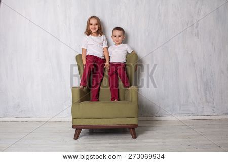 Little Boy And Girl Are Brother And Sister Sit On A Green Chair