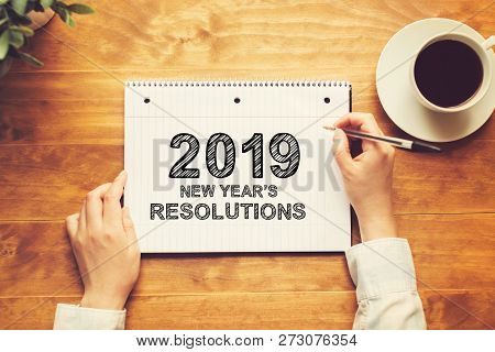 2019 New Years Resolutions With A Person Holding A Pen On A Wooden Desk
