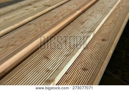 Terrace Boards Larch With Strips, Building Materials In Warehouse. Unpainted Grooved Wood Terrace Pl