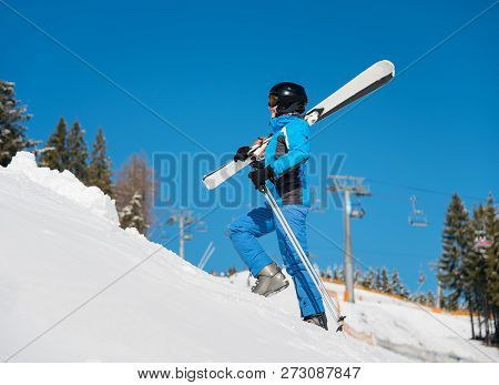 Woman Skier Walking Up The Slope In The Mountains Carrying Her Skis On The Shoulder.