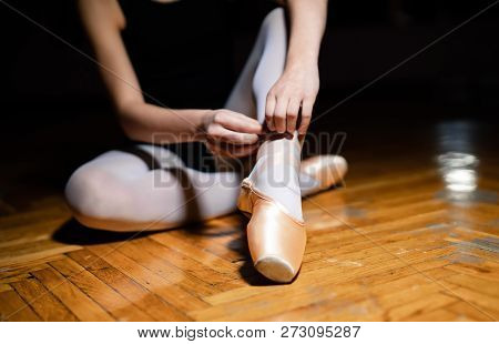 Unknown Ballerina Is Tying The Ribbon Of Pointe Shoes On The Wooden Floor In A Ballet Class. The Bal