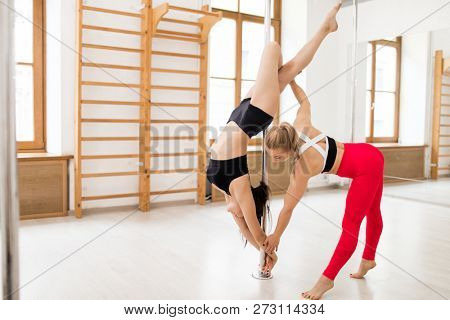 Young poledance coach helping her learner with difficult stretching exercise during workout
