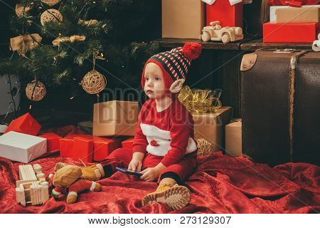 Child With A Christmas Present On Wooden Background. Happy Children. Babies. Winter Kids. Christmas