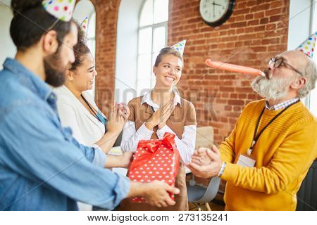 Group of young managers congratulating their senior boss on anniversary right in office