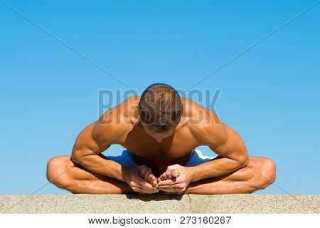 Flexible body is his merit. Mental and physical health. Muscular man sit yoga position. Yoga instructor with muscular body stretching. Sport and health care. Coach demonstrate yoga asana outdoors. poster