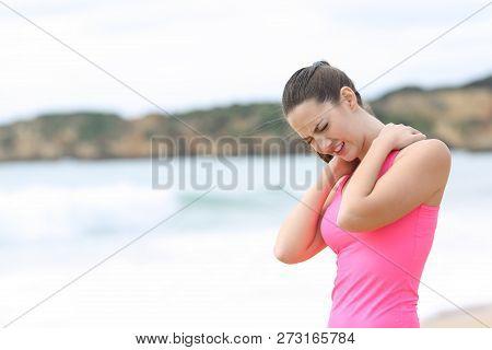Sportswoman Suffering Neck Ache Standing On The Beach