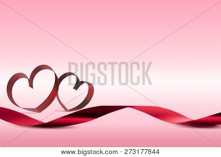 Red Ribbons With Ribbons Shaped As Hearts Over Pink Background. Love Concept And Valentines Day