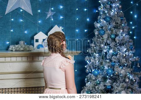 A little girl with a red pigtail stands with her back to the camera and admires the magical decoration of the Christmas tree. Immersion in a fairy tale poster
