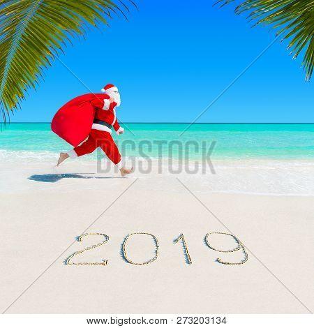 Christmas Santa Claus Run At Ocean Tropical Sandy Palm Beach With Large Sack Full Of Gifts - Season