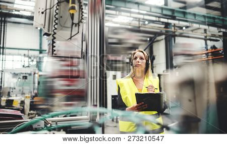 Industrial Woman Engineer With Headset In A Factory, Working. Copy Space.