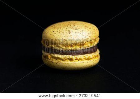 Sweet yellow macaroon isolated on black background.