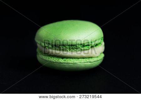 Sweet green macaroon on black background.