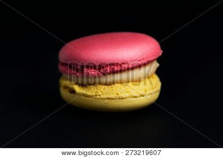 Sweet colored macaroon isolated on black background.