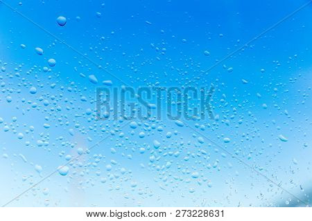 Texture Of Water Droplets On Glass Window In Fall Or Winter Setting. Blurry Background With Water Dr
